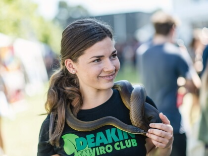 Member of the Deakin College Enviro Club holding a snake