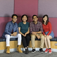 Four students sitting on bench at Deakin