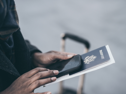 Person holding mobile phone and passport