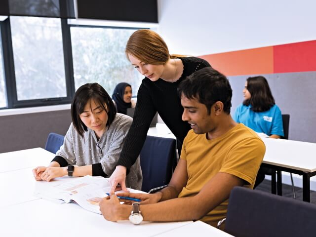 Teacher assisting two students in Deakin College classroom